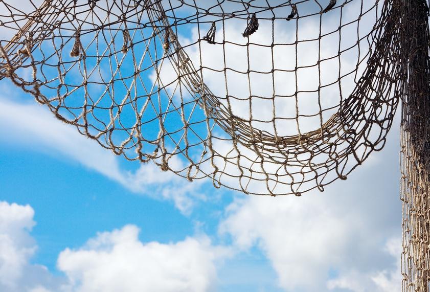 Ein Fischernetz vor blauem Himmel mit weißen Wolken.