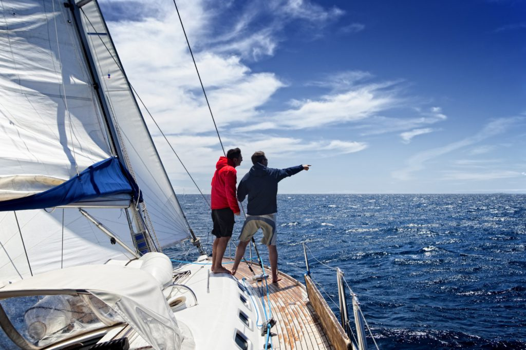 Sailing crew members on sailing ship observing the sea.